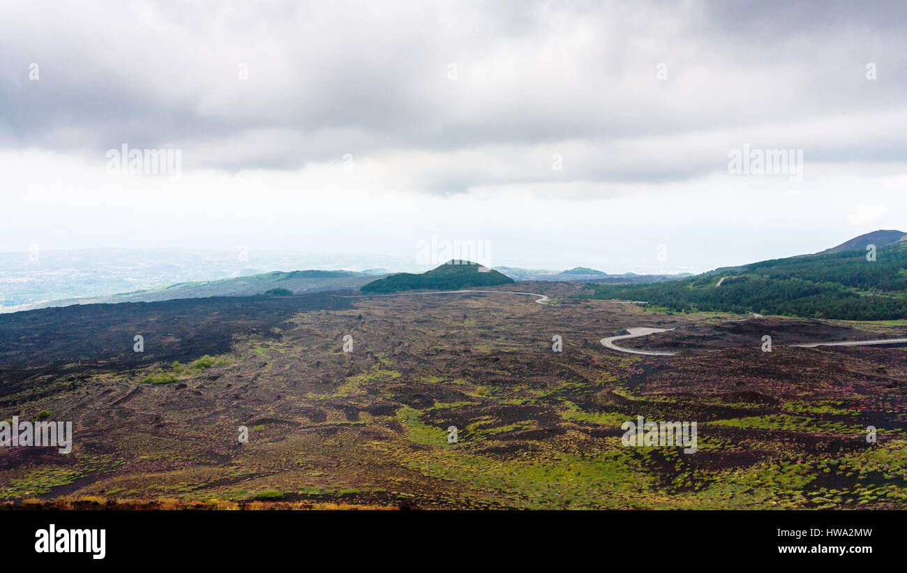 travel to Italy - low cloudy sky over lava fields on Mount Etna in Sicily in summer day - Stock Image