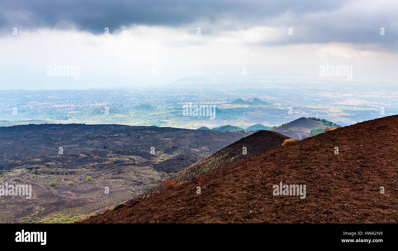 travel to Italy - view of lava fields on Mount Etna and Ionian Sea coast in Sicily in summer day - Stock Image