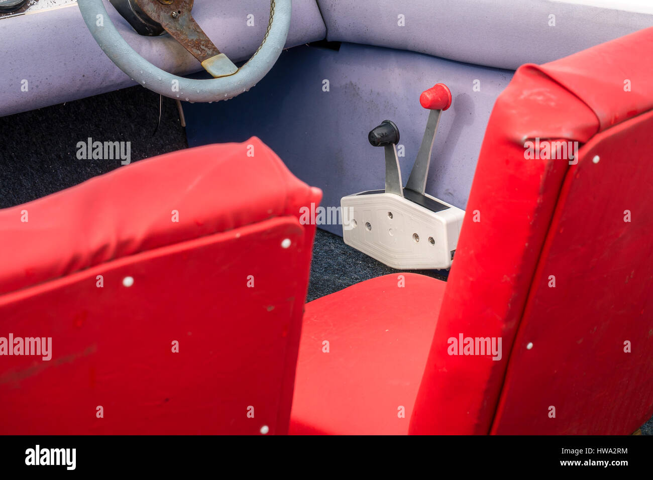 Close up of seats, steering wheel and gear levers inside well used old motorboat, North Berwick, East Lothian, Scotland, - Stock Image