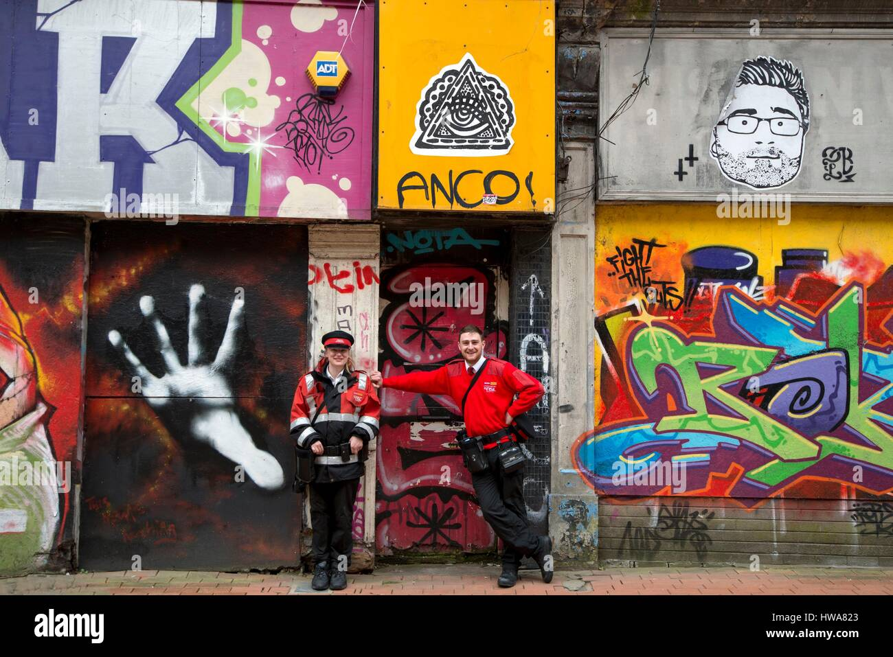 United Kingdom, Northern Ireland, Belfast, Local police pausing in front of graffitis in the city center - Stock Image