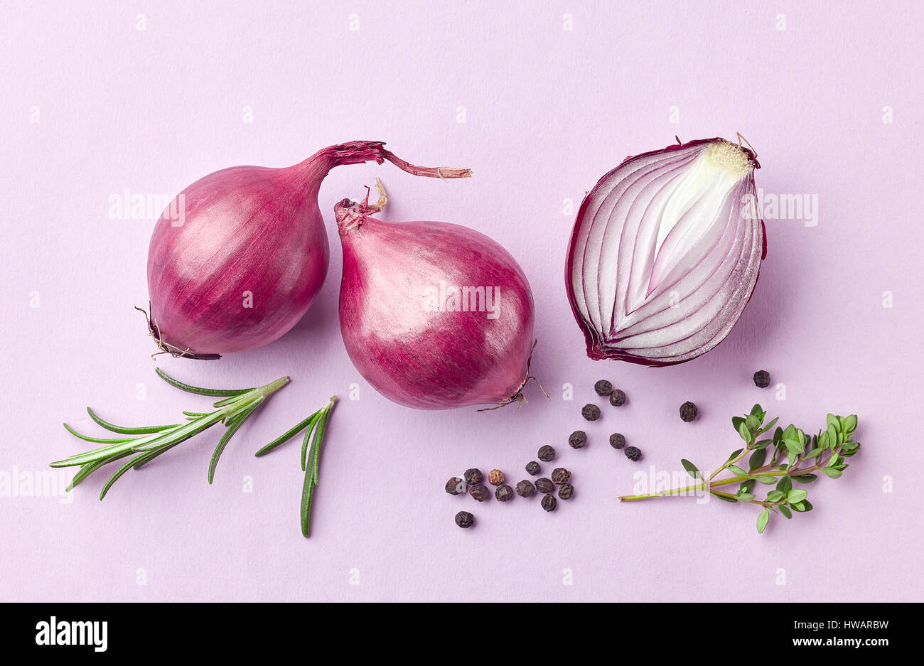 red onions and spices on purple background, top view - Stock Image