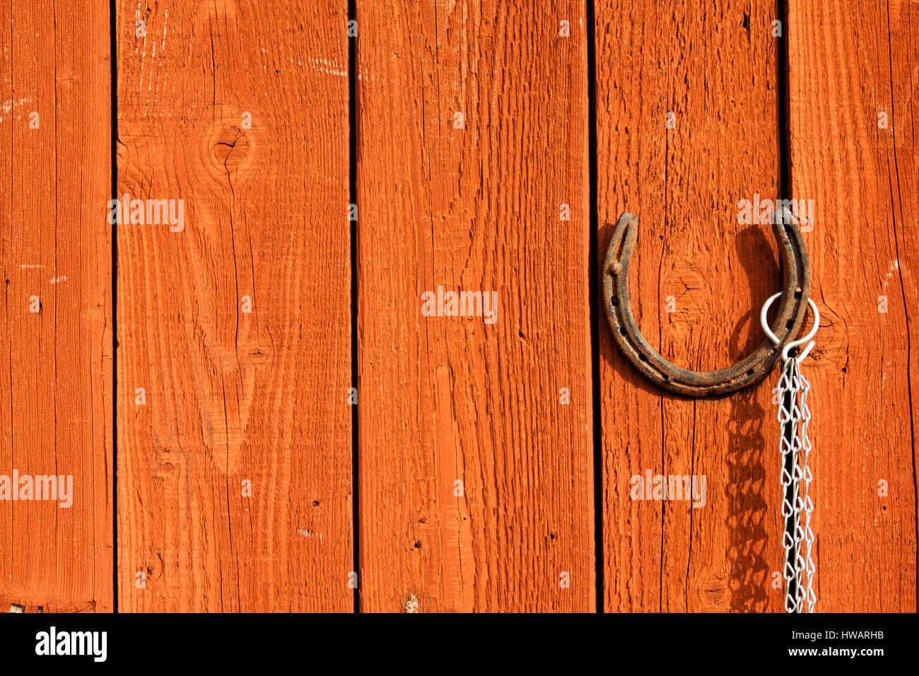 Old Rusty Horseshoe Hanging On A Brown Wooden Door