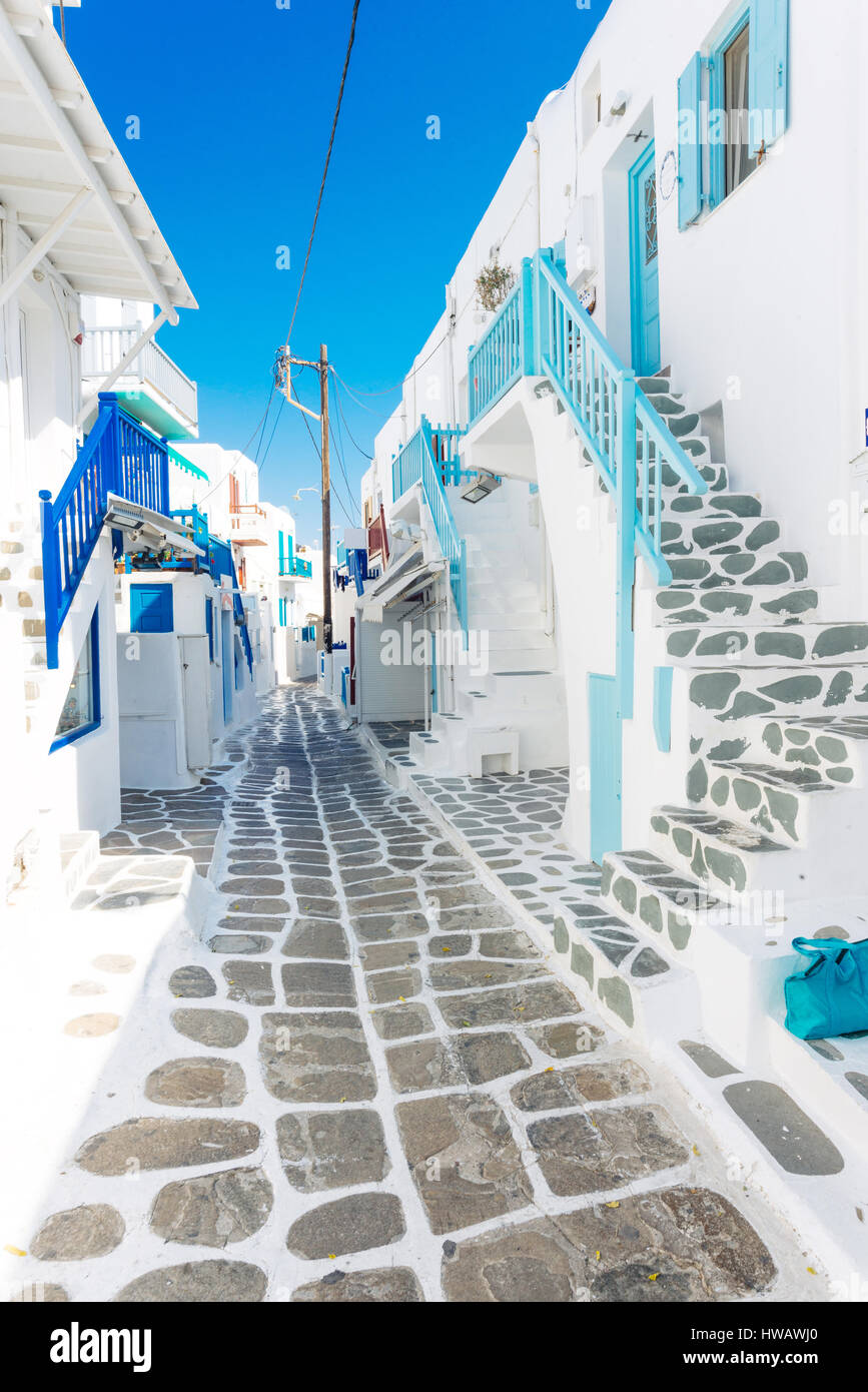Mykonos old town street with cobbled walkways, white walls, and painted door and windows, Mykonos island, Greece Stock Photo
