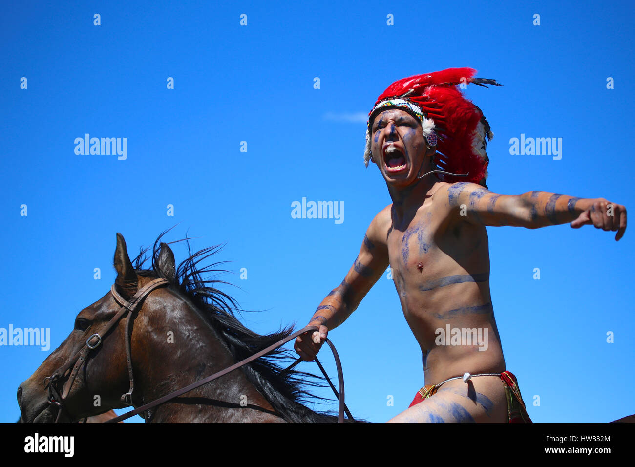 Native American Indian Wearing Blue War Paint And Wearing Red Feather Stock Photo Alamy