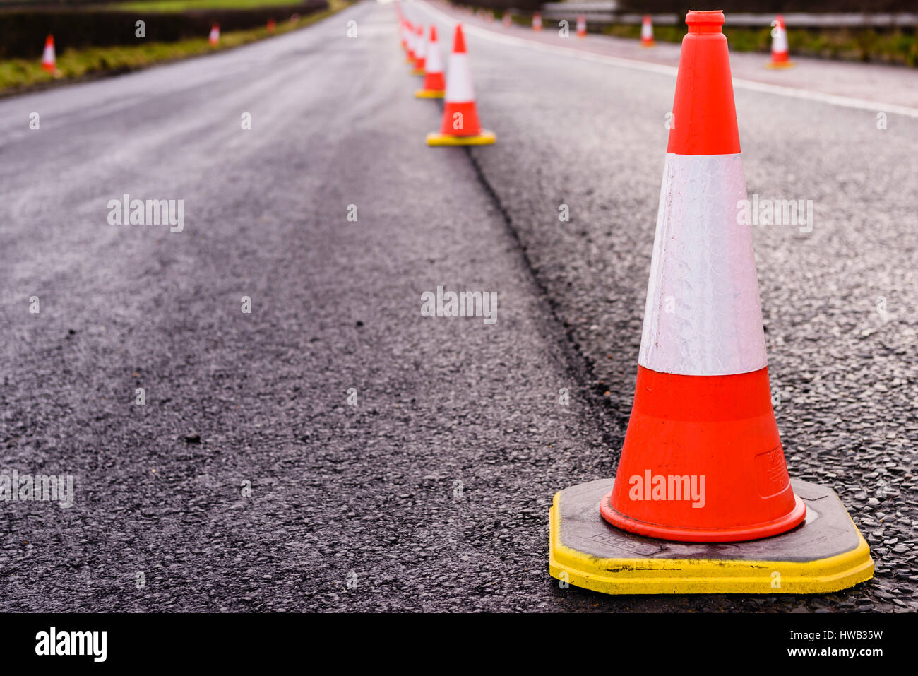 Row of traffic cones along the middle of a road being resurfaced. - Stock Image