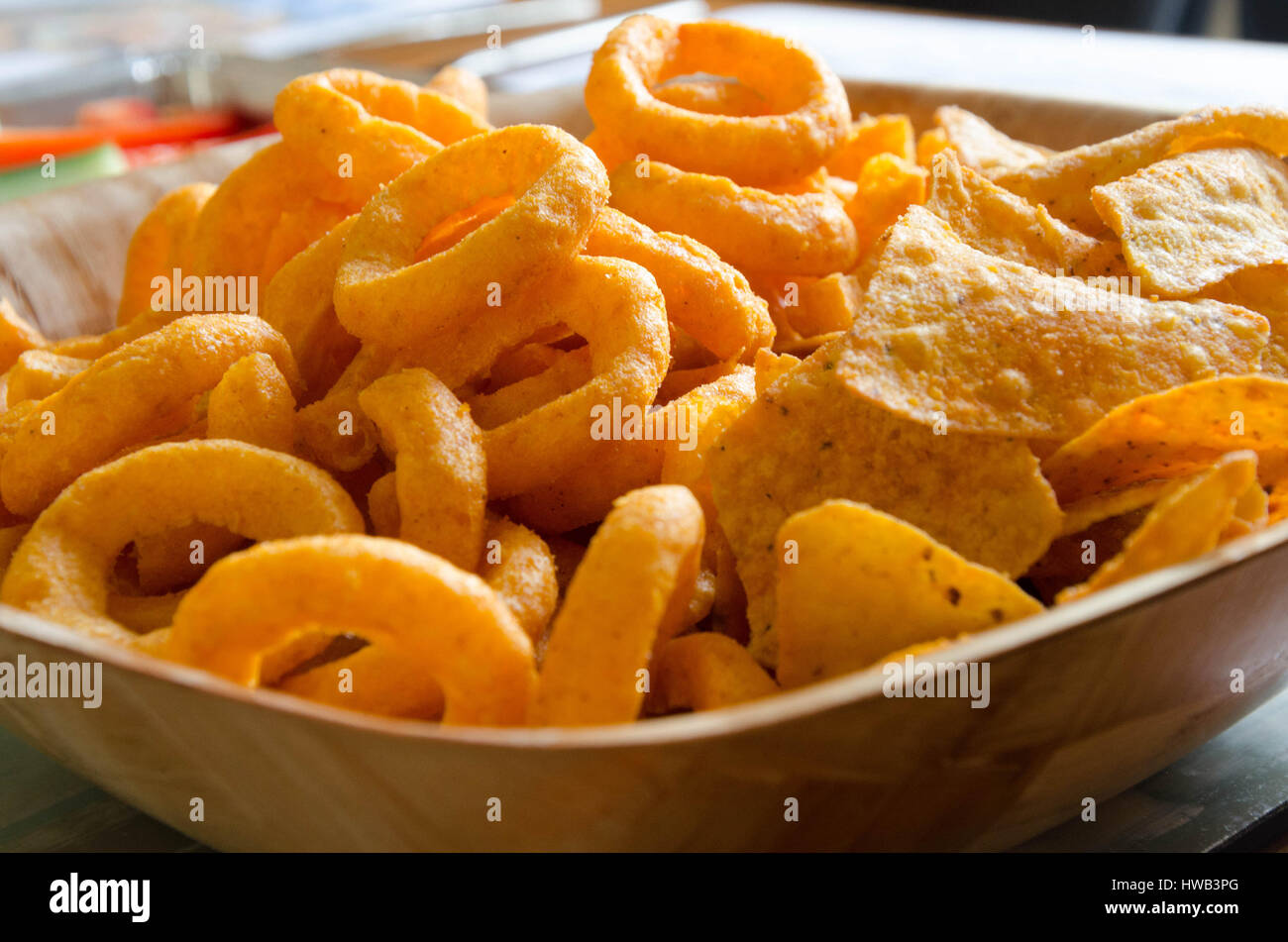 A closeup of a bowl of onion ring and tortilla crisps. - Stock Image