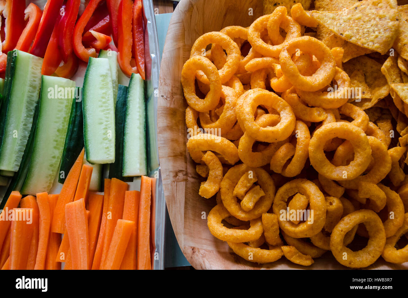 Healthy and unhealthy food snack choices with crisps and raw vegetable sticks seen side by side from above. - Stock Image