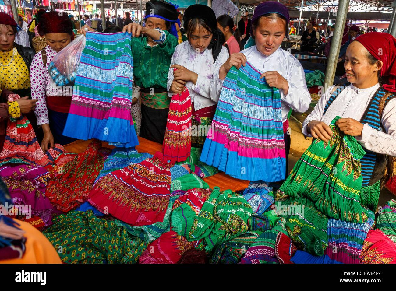 Vietnam, Ha Giang Province, Dong Van, Hmong women buying traditional skirts at the market - Stock Image