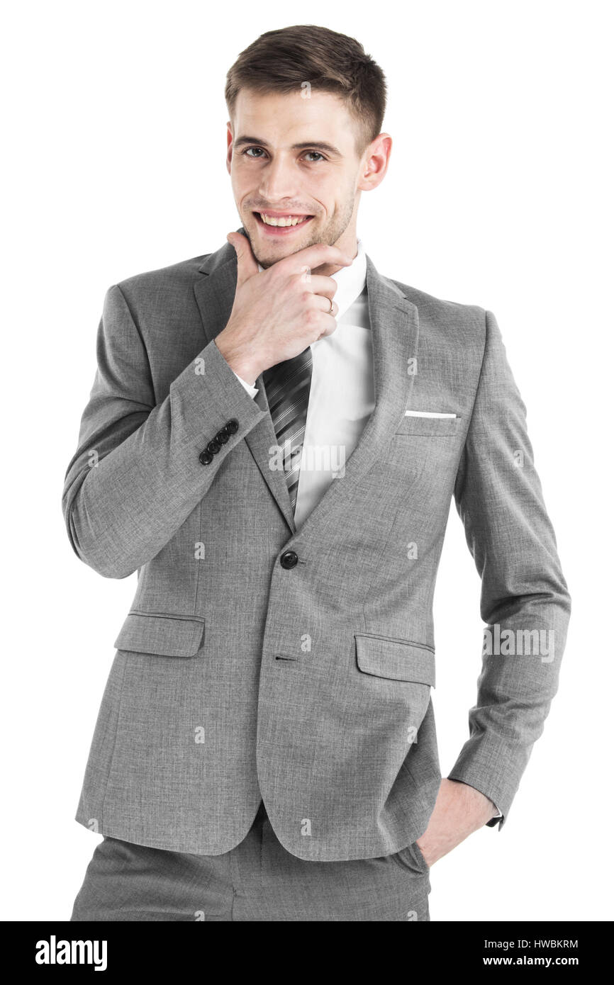 Portrait of handsome smiling young business man holding hand on chin isolated on white background - Stock Image