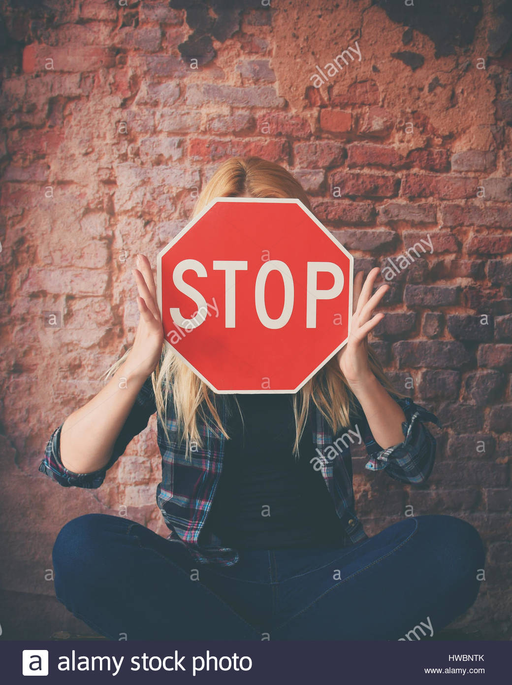 A young girl is holding a stop sign to her face for a concept of violence, hate or texting while driving. - Stock Image