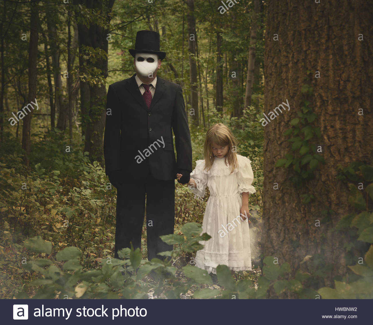 A scary man in a white mask and suit is standing in the dark woods with a child who is possessed with evil for a - Stock Image