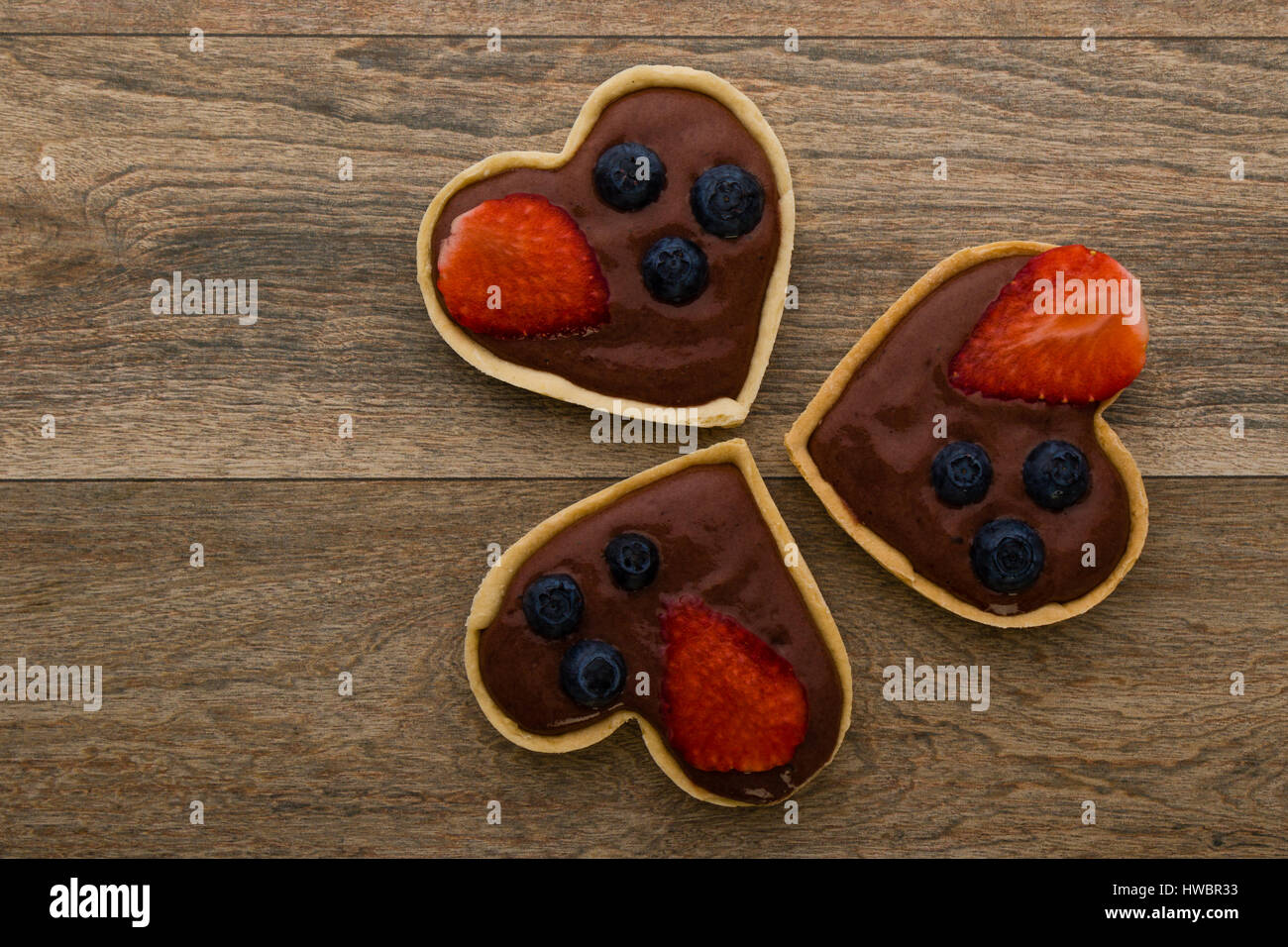 heart shape chocolate tart with strawberry and blueberry - Stock Image