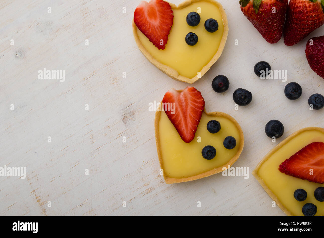 heart shape vanilla tart with strawberry and blueberry on white table - Stock Image
