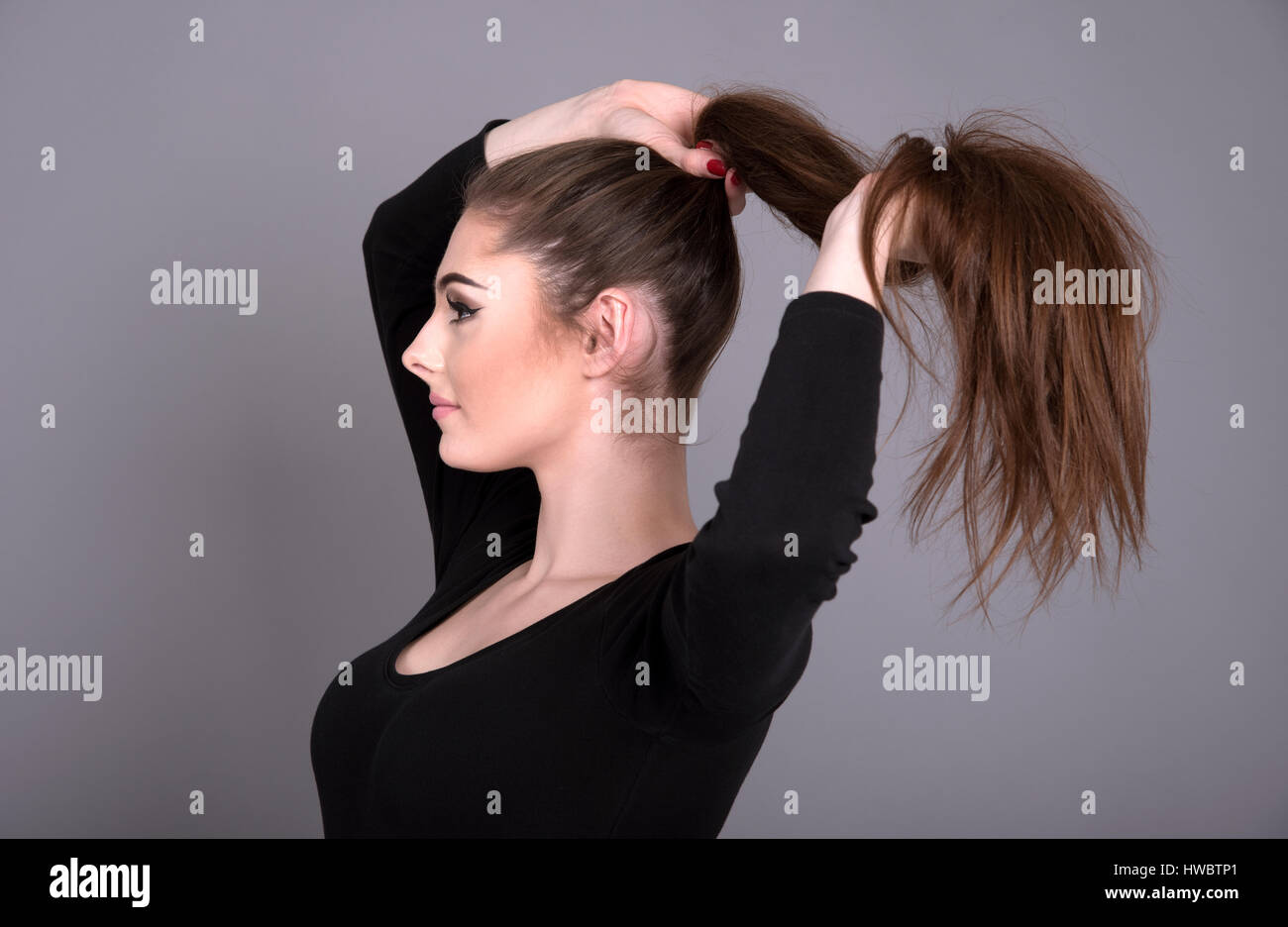 Young woman holding her long dark coloured hair in a pony tail - Stock Image