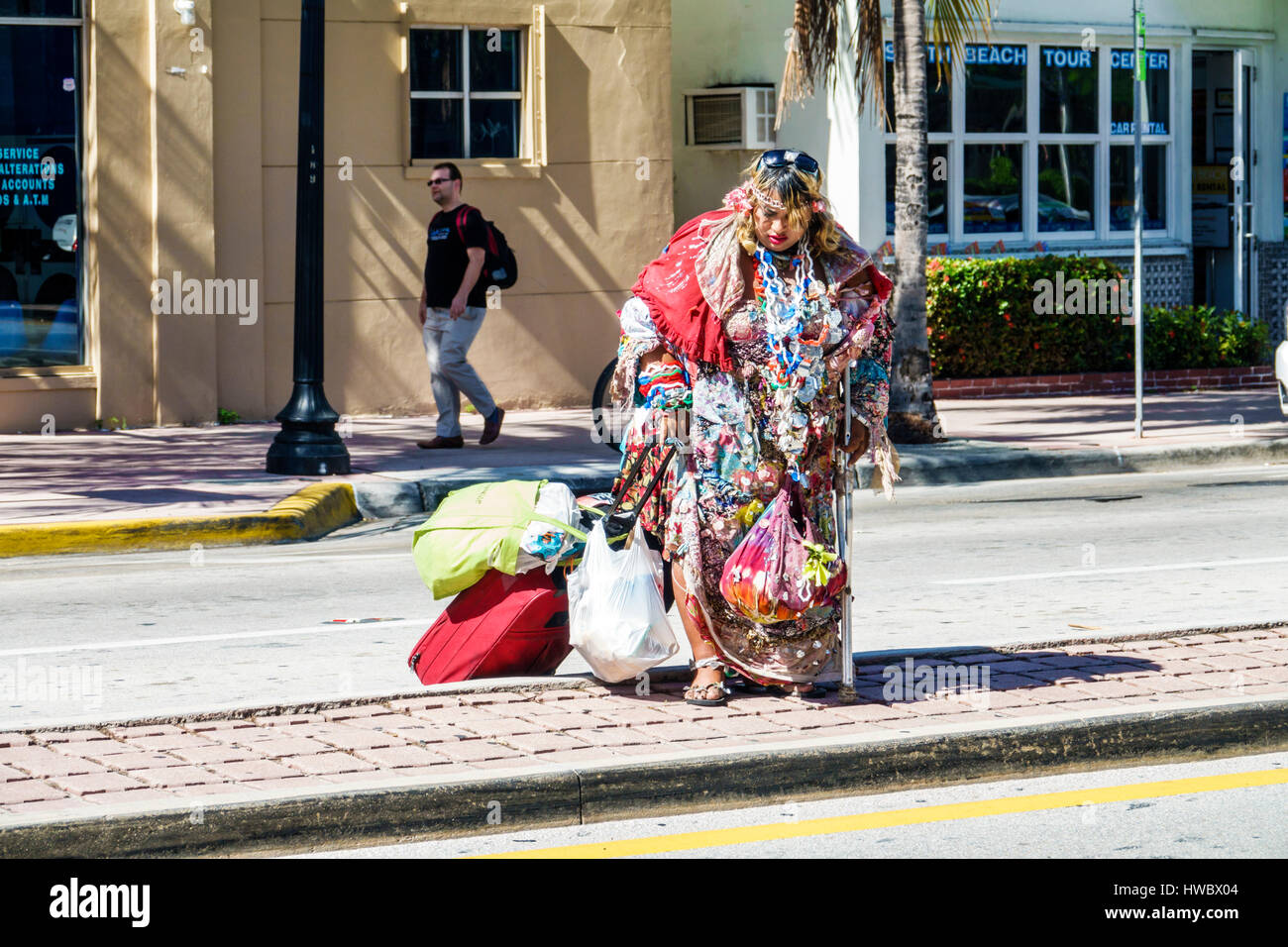 Miami Beach Florida Washington Avenue woman bag lady young adult homeless indigent street person eccentric rolling - Stock Image
