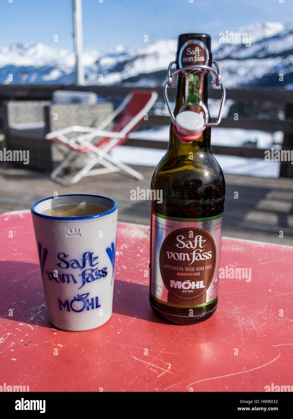 Bottle of non-alcoholic Möhl Apfelwein 'Saft vom Fass', a traditional Swiss cider, with a ceramic beaker. - Stock Image