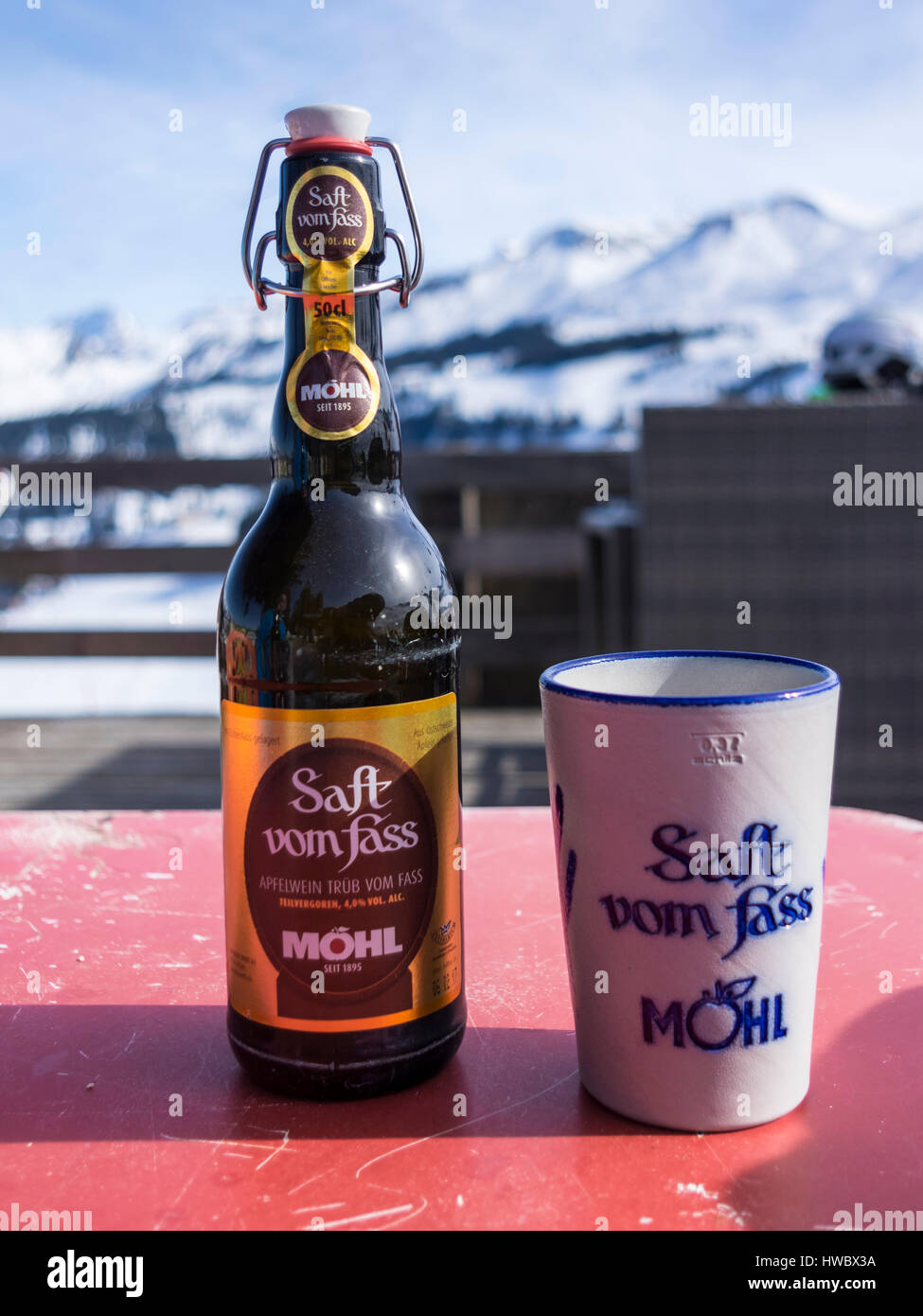 Bottle of Möhl Apfelwein 'Saft vom Fass', a traditional Swiss cider, with a ceramic beaker. Alpine - Stock Image