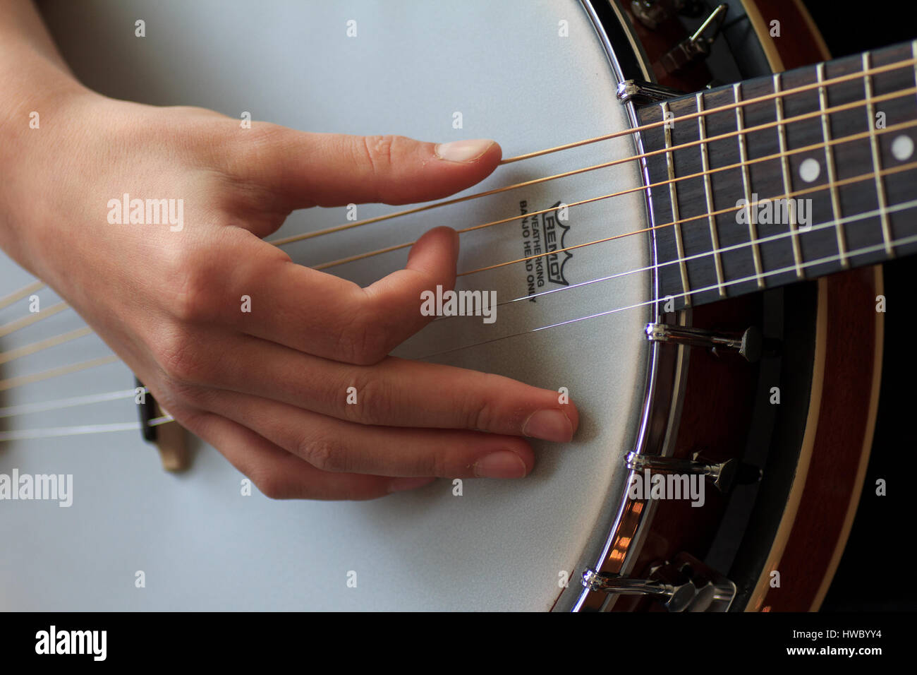 Hand of banjo player picking strings on banjo - Stock Image