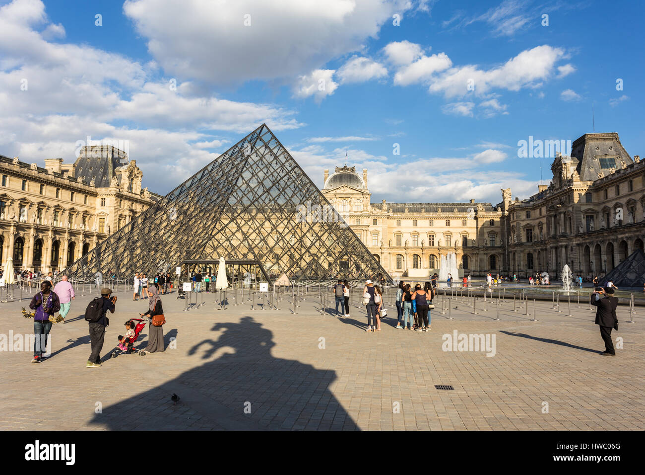 PARIS - AUGUST 6, 2016: Tourists take pictures in the Louvre Palace on a sunny day in Paris, France capital city. - Stock Image