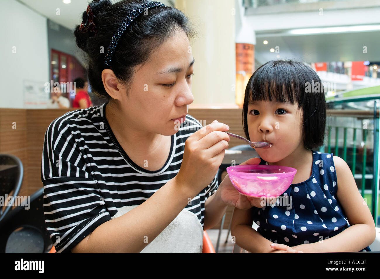 Asian Mother Feeding Her Daughter in Outdoor Cafe - Stock Image