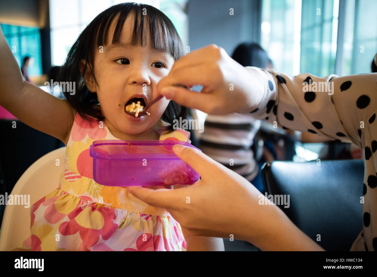 Asian Mother Feeding Kid Daughter Food in a Restaurant - Stock Image