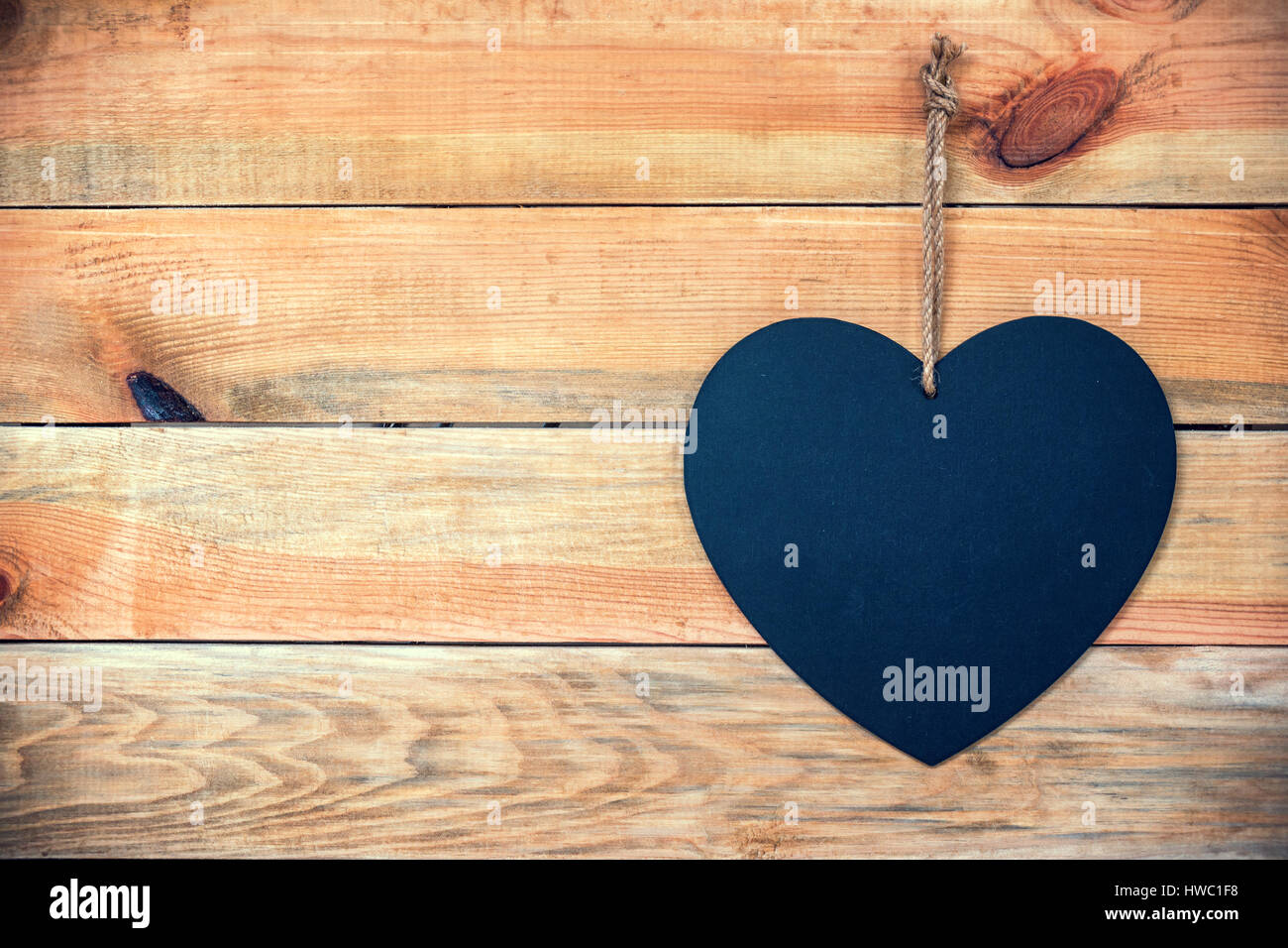 Wood planks with a chalkboard in the shape of a  heart, love greeting card background with copy space for text - Stock Image
