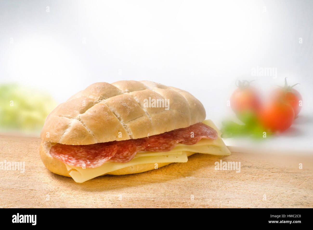 inviting sandwich with salami and cheese on wooden desk with blurred foggy tomatos and lettuce background - Stock Image
