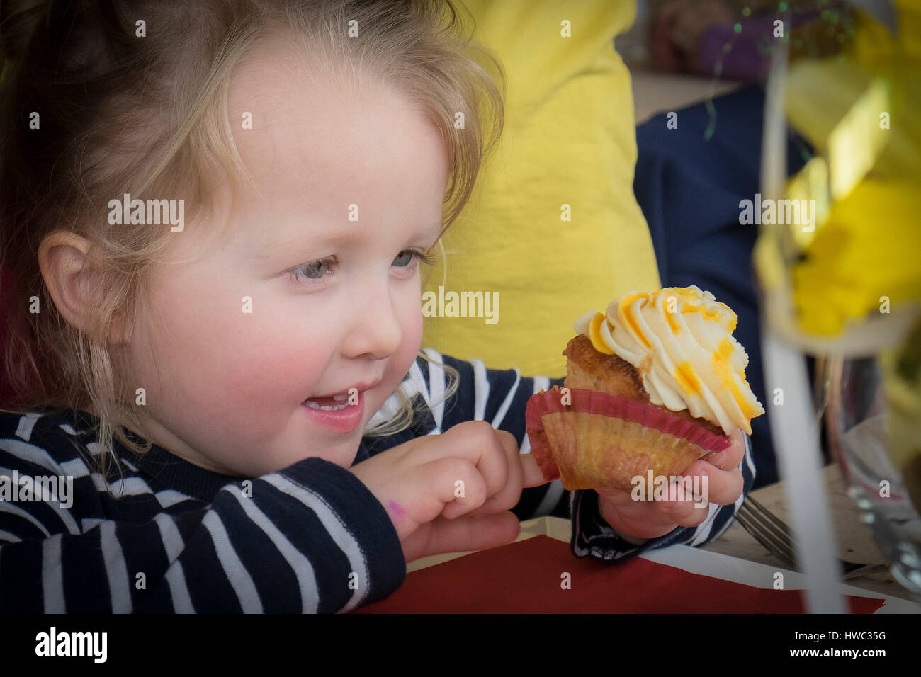 Pretty Blond Child Girl Young Enjoying Anticipating Cake Cupcake - Stock Image