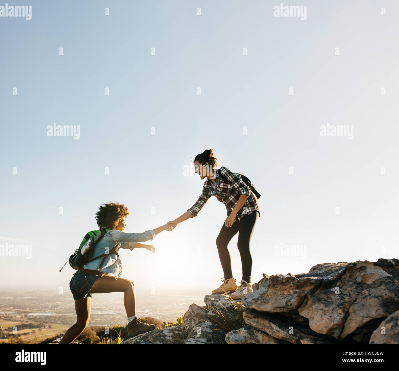 Helping Each Other: Female Friends Hiking Help Each Other In Mountains. Young