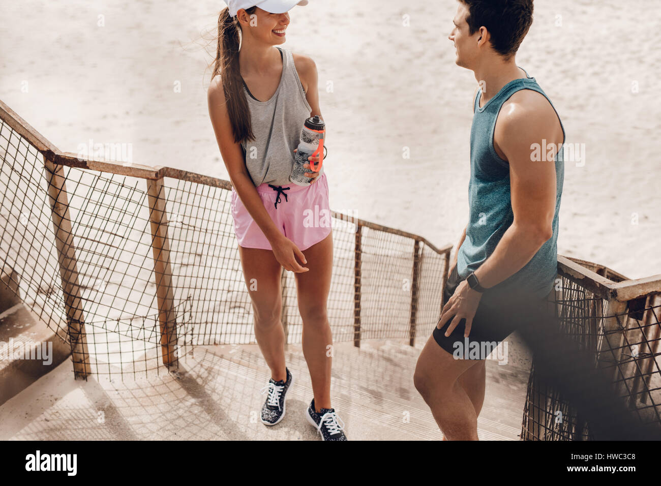 Outdoor shot of young man and woman resting after morning run at the beach. Couple relaxing and talking during workout - Stock Image
