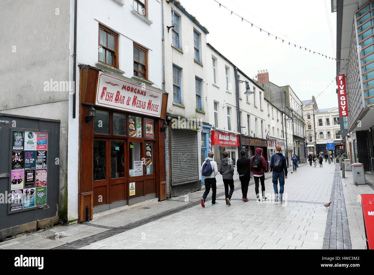 View of 5 young men walking past Five Guys fast food restaurant on Caroline Street in Cardiff City Centre, Wales Stock Photo