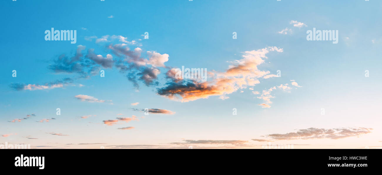 Panorama Of Bright Blue Sky With White Fluffy Clouds. Blue Sunny Cloudscape At Sunset Or Sunrise Background - Stock Image