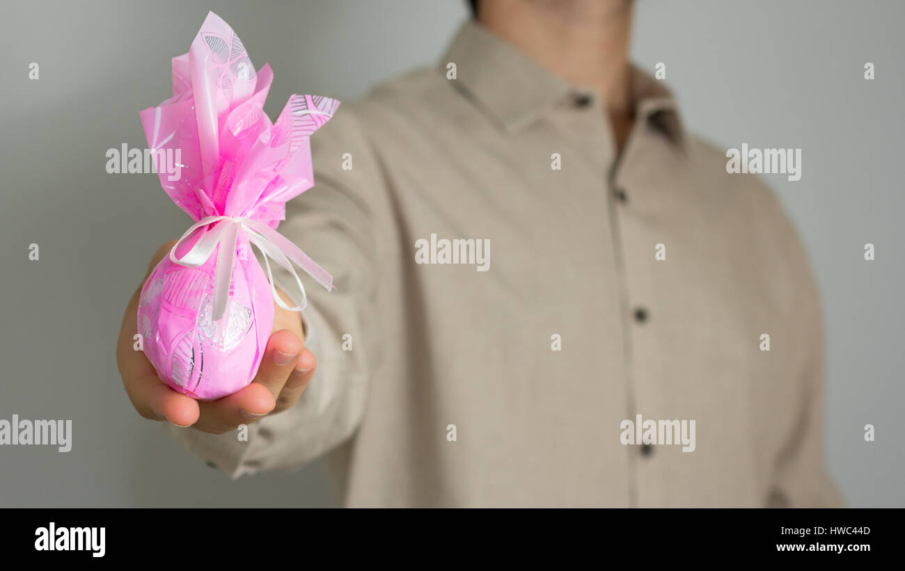 Man presents small Easter egg, pink packinging. Slim man wearing social shirt of neutral color, gray background. - Stock Image
