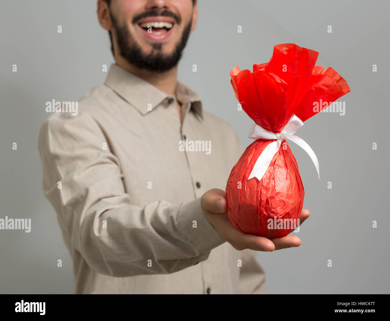 Young man presents homemade Easter egg, packed in red paper. Slim man wearing social shirt of neutral color, gray - Stock Image