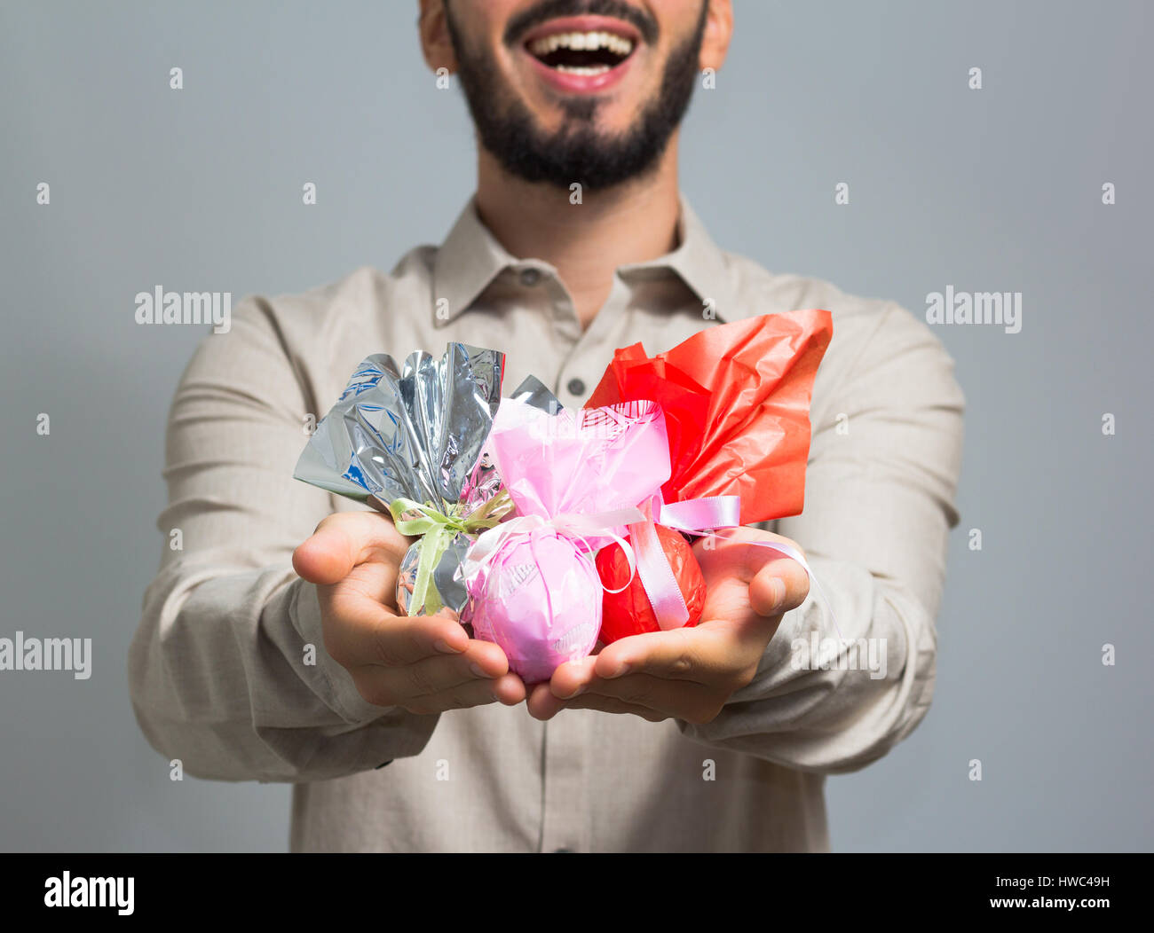 Man handing assorted easter eggs with a big smile on his face. Slim man wearing social shirt of neutral color, gray - Stock Image