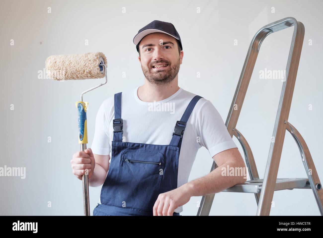 Man ready to paint a wall holding painting tools - Stock Image