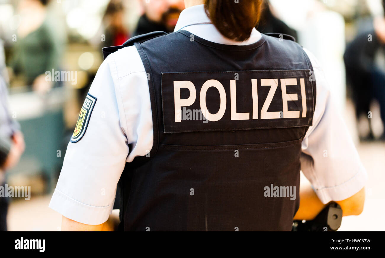German police officer woman on the Hamburg airport observes passengers. Back shot focus on bulletproof vest with - Stock Image