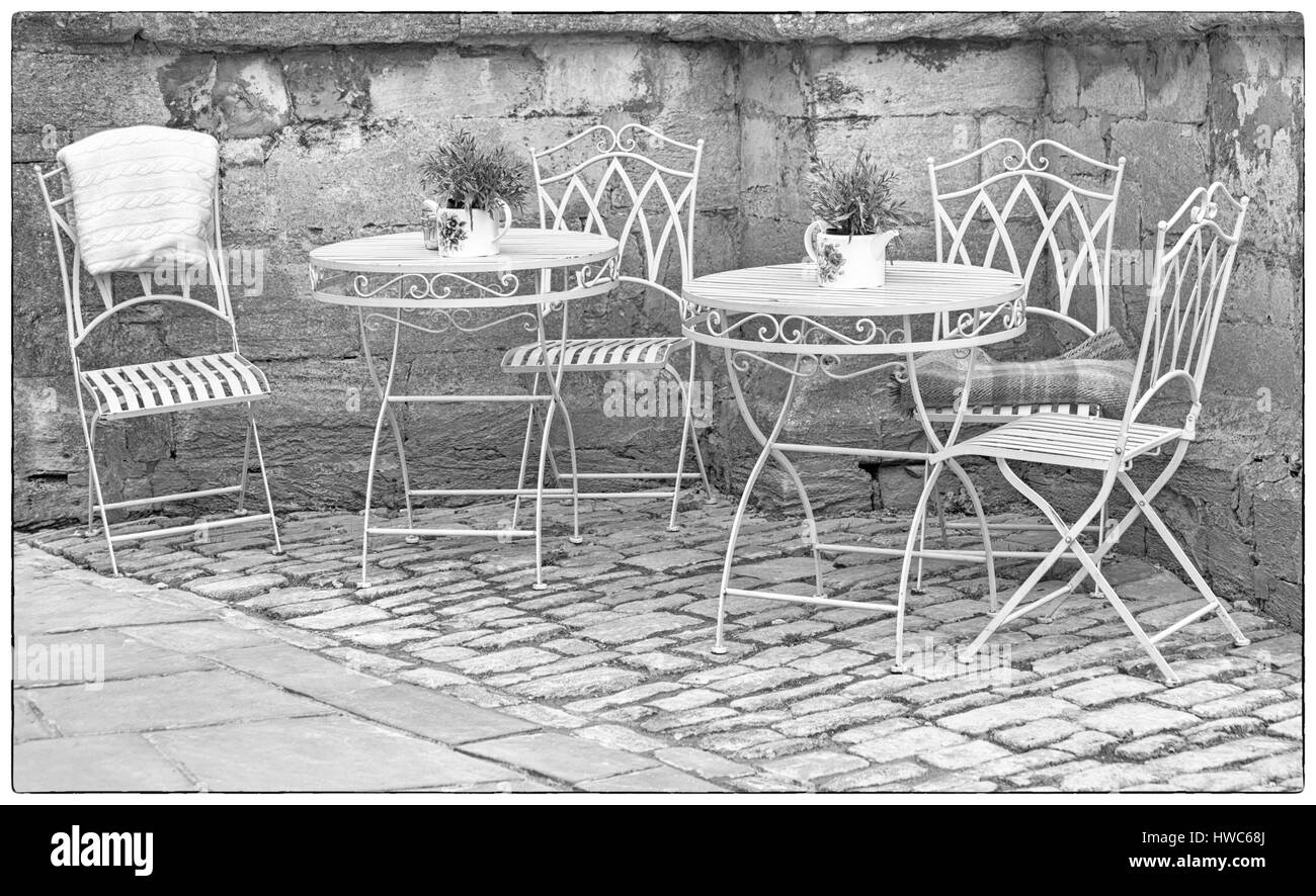 Cirencester - ornate wrought iron tables and chairs with plant pots in a corner of Cirencester, Gloucestershire - Stock Image