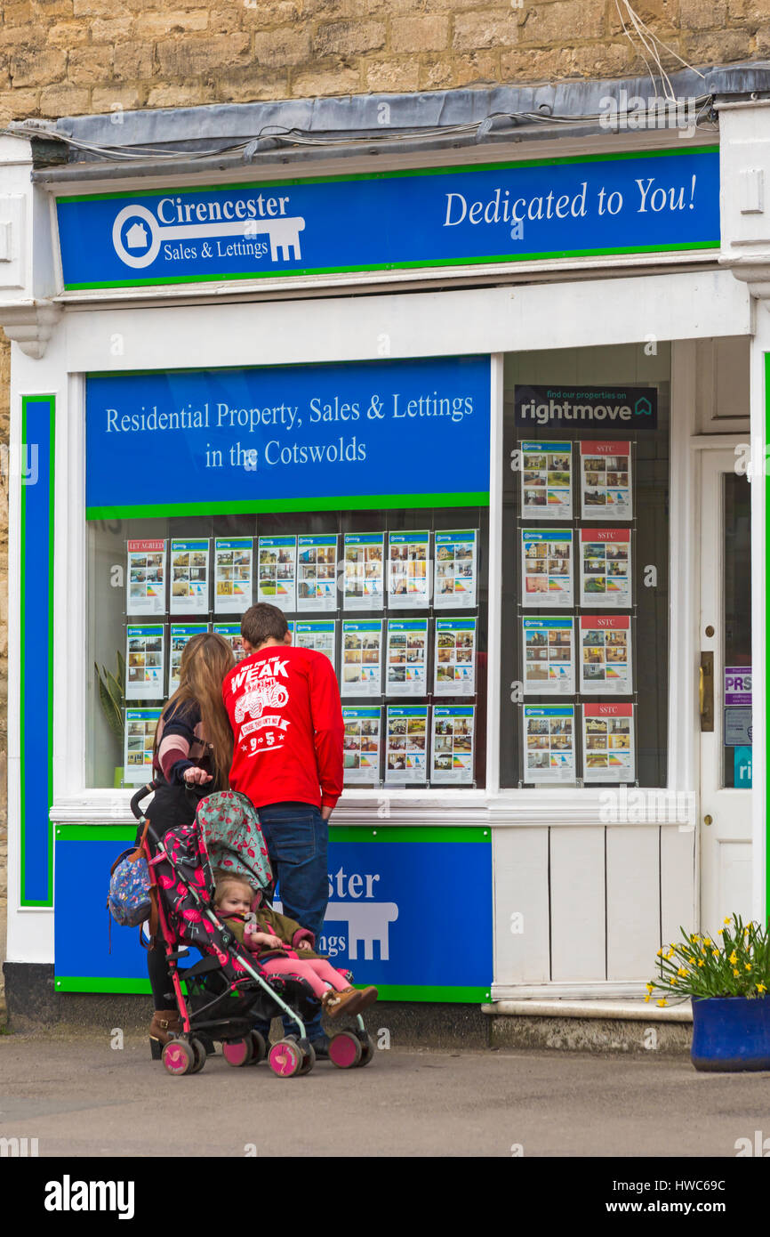 Cirencester - Couple with toddler in pushchair looking at properties in window of Cirencester Sales & Lettings, - Stock Image