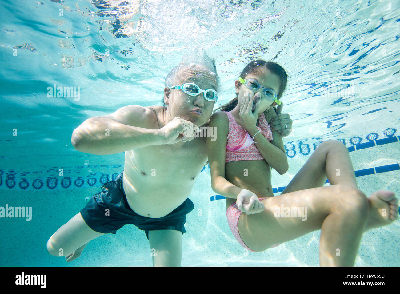 Grandfather swims in the pool with his grandaughter Stock Photo