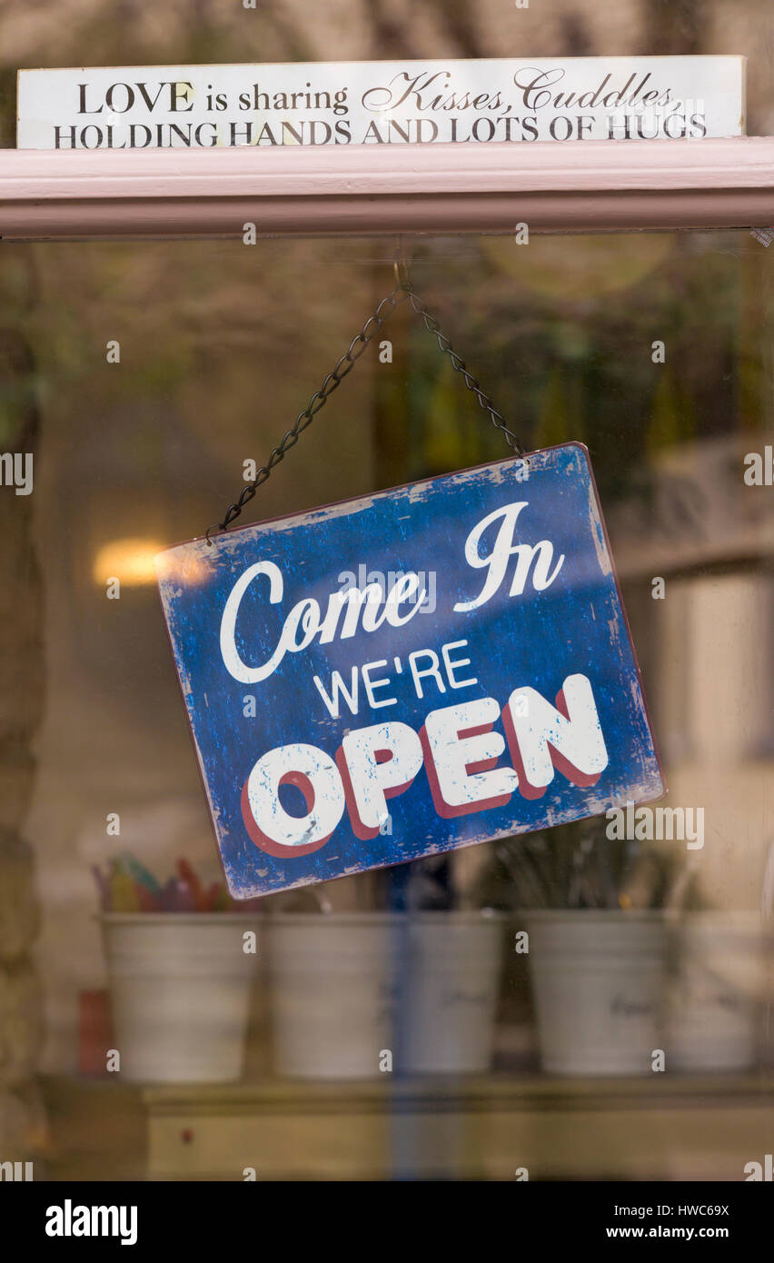 Cirencester - Come in we're open sign hanging on door of shop at Cirencester, Gloucestershire in March Stock Photo