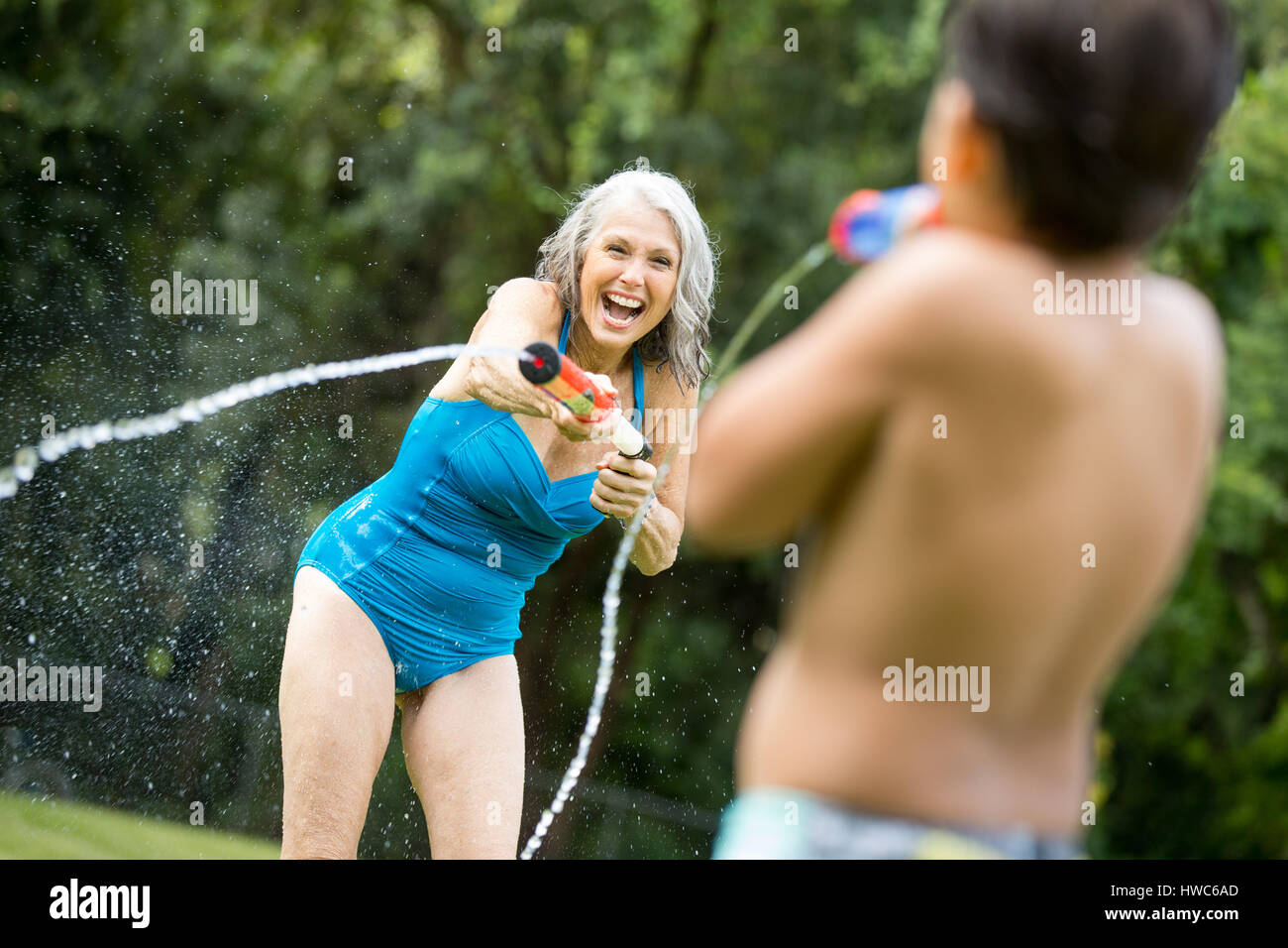 Grandmother playing with grandchildren with waterguns - Stock Image
