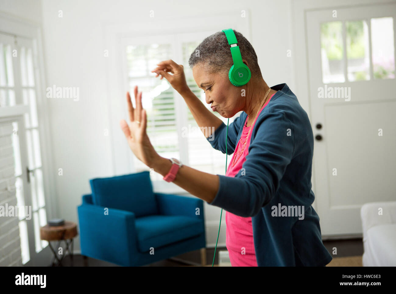 Senior woman listening to music on headphones - Stock Image