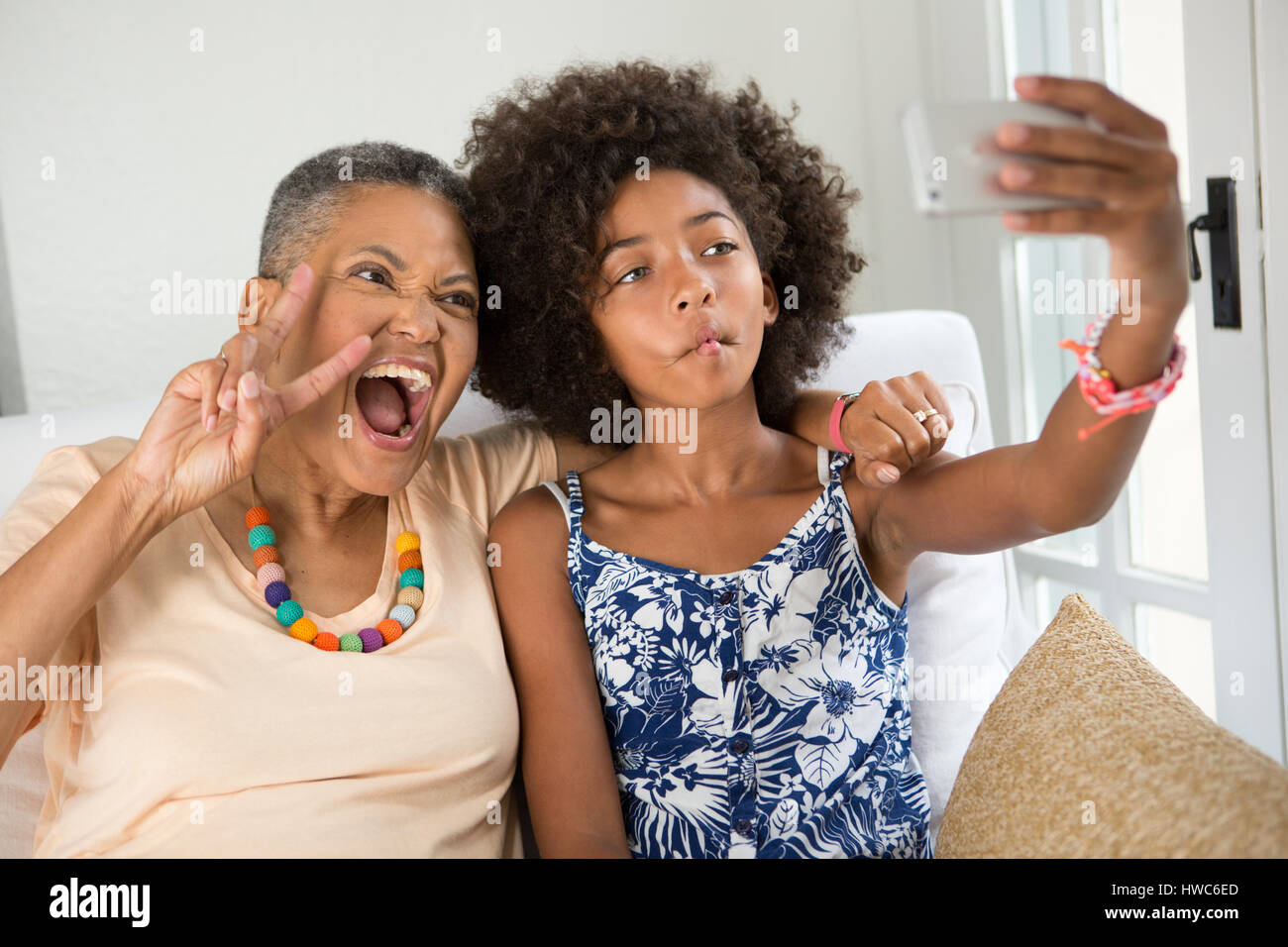 Girl teaching grandmother how to take a selfie - Stock Image