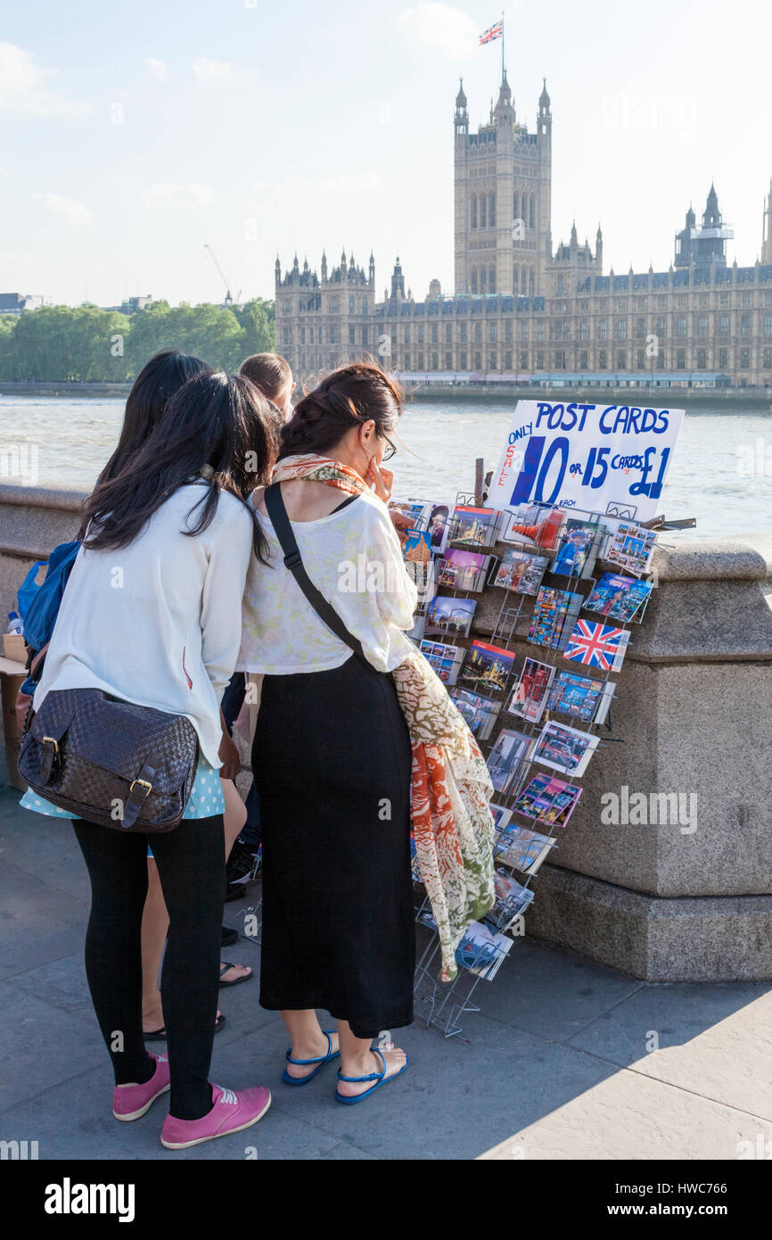 People buying postcards for sale by the River Thames in London, England, UK - Stock Image