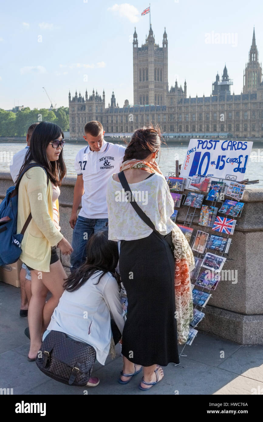 Young tourists choosing postcards for sale by the River Thames in London, England, UK - Stock Image