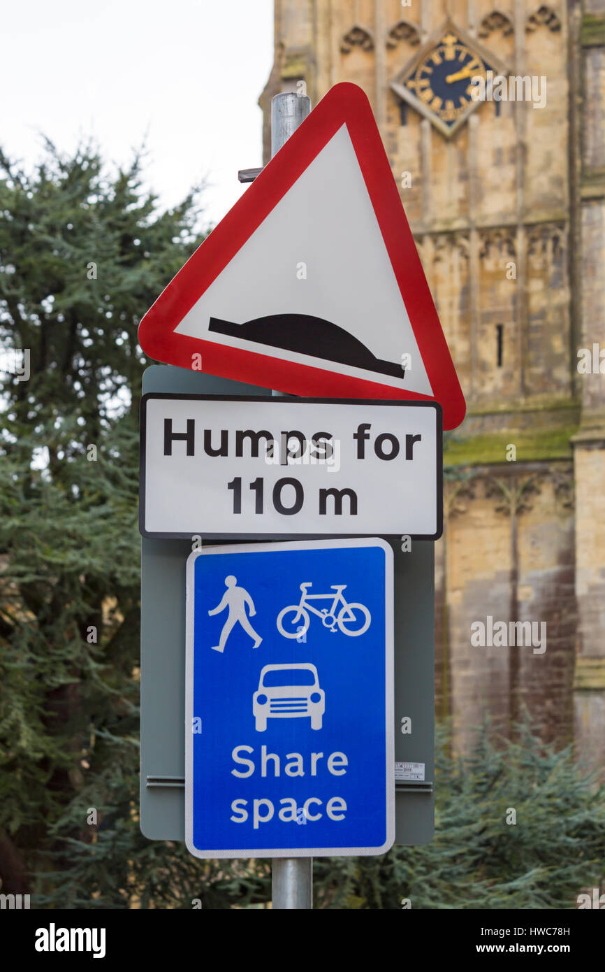 Cirencester - Humps for 110m and Share space road signs by St John the Baptist Church at Cirencester, Gloucestershire - Stock Image