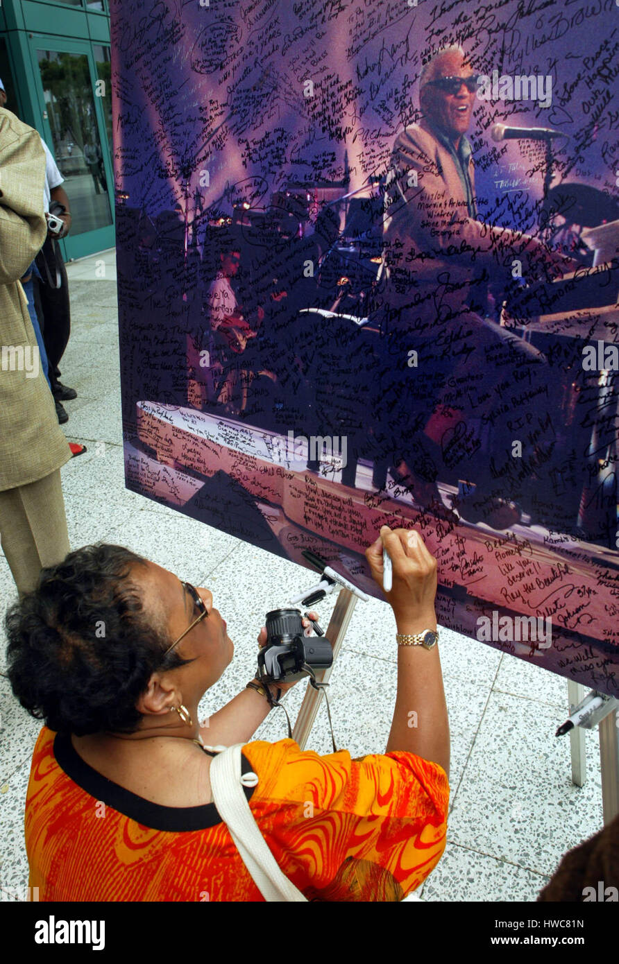 Cora Crenshaw  signs a poster for singer Ray Charles outside  the Los Angeles Convention Center where there is a - Stock Image