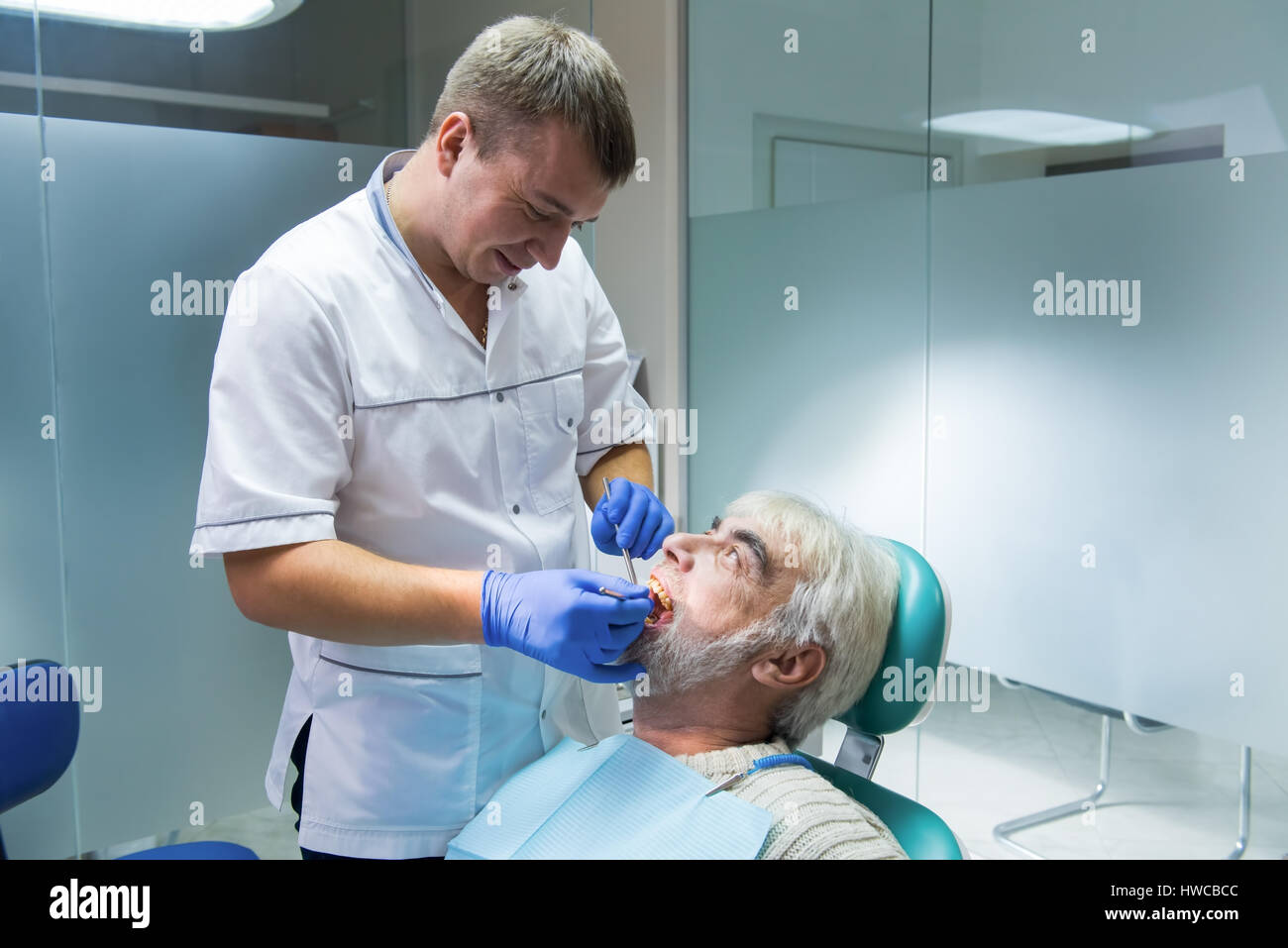 Dental doctor with senior patient. - Stock Image