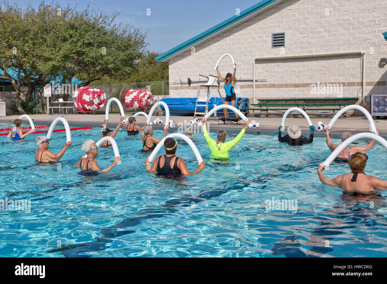 Group of women attending Water Aerobics class, Instructor demonstrating,  using  styrofoam 'water noodle', - Stock Image